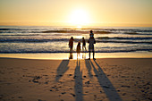 Family wading in summer ocean surf at sunset