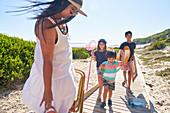 Happy family on sunny beach boardwalk