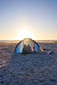 Silhouette family inside tent on sunset beach