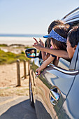 Happy kids leaning out car window at beach