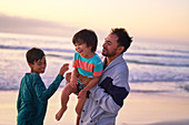 Happy father and sons playing on ocean beach