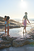 Brother and sisters playing in ocean tide pool