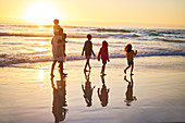 Family walking in ocean surf on beach at sunset
