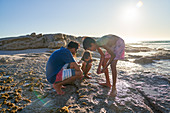 Family playing on rocks on sunny beach