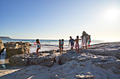 Family playing on ocean beach, South Africa