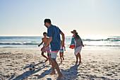 Family playing soccer on sunny ocean beach