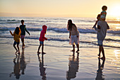 Family playing in ocean surf at sunset