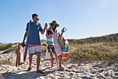 Playful family walking in sand on sunny beach path