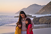 Affectionate mother and daughters hugging on beach