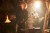 Female blacksmith working in sunny workshop