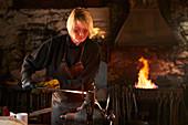 Female blacksmith working in workshop