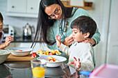 Family eating fruit in kitchen