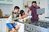 Father with laptop feeding kids with take out food