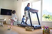 Kids running around mother exercising on treadmill