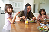 Mother and daughters eating lunch at table