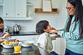 Mother wiping face of son eating fruit in kitchen