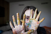 Close up girl with finger paint covering hands