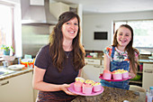 Portrait mother and daughter baking cupcakes