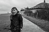Portrait muddy boy on rural footpath