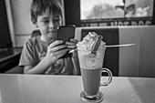 Boy with smart phone enjoying milkshake in diner