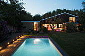 Home showcase exterior with swimming pool at night