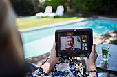 Woman video chatting with friends at poolside