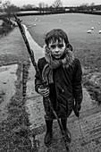 Portrait muddy boy with stick in rural field