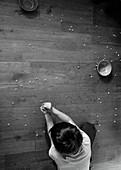 Boy picking up spilled cereal on hardwood floor