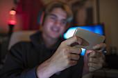 Teenage boy using smart phone in dark bedroom