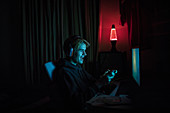 Boy playing videogame at computer in dark bedroom