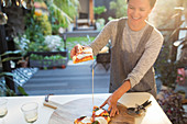 Smiling woman eating homemade pizza on patio