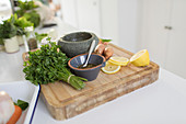 Cilantro and lemons on cutting board with mortar