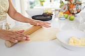 Woman rolling out pie dough with rolling pin