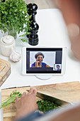 Woman cooking and video chatting with friends