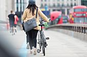 Businesswoman walking bicycle, London, UK