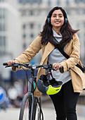 Smiling woman walking bicycle