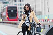 Businesswoman on bicycle, London, UK