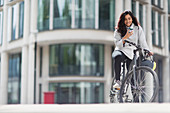 Smiling woman using smart phone on bicycle in city