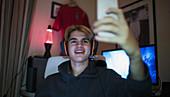 Smiling teenage boy taking selfie with smart phone