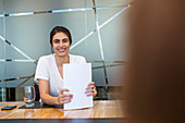Portrait Businesswoman with paperwork in meeting