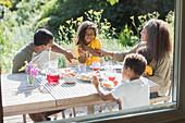 Happy family enjoying lunch on sunny summer patio