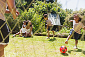 Happy family playing soccer in summer backyard