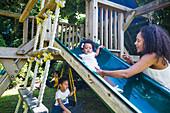 Mother watching toddler daughter on slide