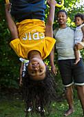 Portrait playful girl hanging upside down