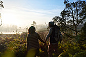 Young couple hiking in tranquil foggy landscape