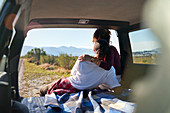 Couple enjoying nature view from back of car