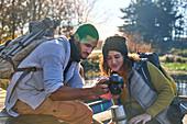 Young hiking couple using digital camera