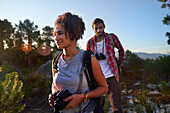 Couple hiking with camera and binoculars in nature