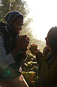 Happy hiker couple drinking coffee in sunny woods
