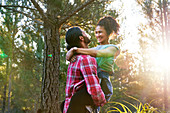 Affectionate man holding happy girlfriend in woods